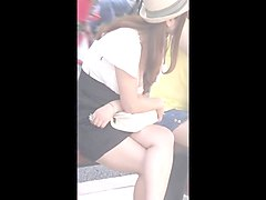nice downblouse girl beside her boyfriend at the bus stop